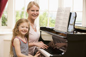 Woman and young girl playing piano and smiling — Stock Photo