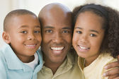 Man and two young children embracing and smiling — Stock Photo