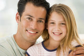 Man and young girl in living room smiling — Stock Photo