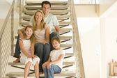 Family sitting on staircase smiling — Stock Photo