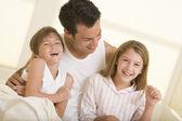 Hombre con dos niños pequeños, sentado en la cama sonriendo — Foto de Stock