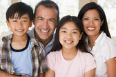 Family in living room smiling — Stock Photo