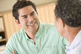 Two men sitting in living room talking and smiling — Stock Photo