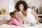 Vrouw en jonge meisje in keuken met cake en koffie glimlachen — Stockfoto