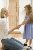 Woman in front hallway holding young girl's hands and smiling — Stock Photo