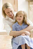 Woman in front hallway hugging young girl and smiling — Stock Photo