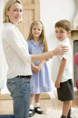Woman in front hallway with two young children smiling — Stock Photo