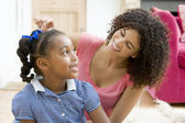 Woman in front hallway fixing young girl's hair and smiling — Stock Photo