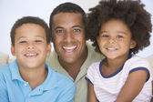 Man and two young children sitting in living room smiling — Stock Photo