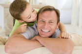Young boy kissing smiling man in living room — Stok fotoğraf