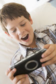 Young boy with handheld game indoors — Stok fotoğraf
