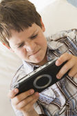 Young boy with handheld game indoors looking unhappy — Stock Photo