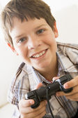 Young boy holding video game controller smiling — Stock Photo