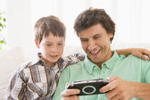 Man and young boy with handheld game smiling — Stock Photo