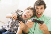 Man and young boy with video game controllers smiling — Stok fotoğraf