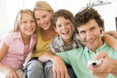 Family in living room with remote control smiling — Stock Photo