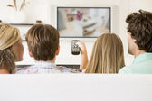 Family in living room with remote control and flat screen televi — Stok fotoğraf