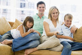 Family sitting in living room with remote control smiling — Stok fotoğraf