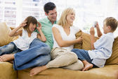 Family sitting in living room with digital camera smiling — Stock Photo