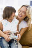 Woman and young girl in living room with video game controllers — Stock Photo