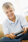 Young boy in living room with handheld video game smiling — Stock Photo