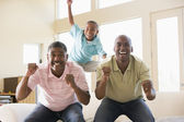 Two men and young boy in living room cheering and smiling — Stock Photo