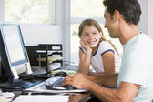 Man and young girl in home office with computer smiling — Stock Photo