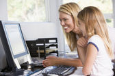 Woman and young girl in home office with computer smiling — Stock Photo