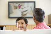 Man and young boy in living room with flat screen television smi — Stock Photo