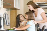 Woman and two young girls in kitchen with computer smiling — Stock Photo