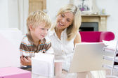 Woman and young boy in home office with laptop smiling — Stock Photo
