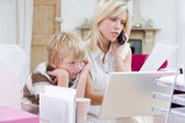 Woman using telephone in home office with laptop while young boy — Stock Photo