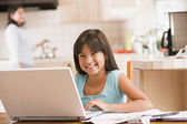 Young girl in kitchen with laptop and paperwork smiling with wom — Stock Photo