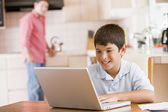 Young boy in kitchen with laptop and paperwork smiling with man — Stock Photo