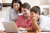 Family in kitchen with laptop smiling — Stock Photo