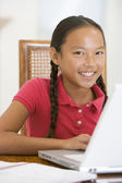 Young girl with laptop in dining room smiling — Stok fotoğraf