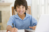 Young boy with laptop doing homework in dining room smiling — Stock Photo