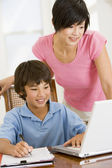 Woman helping young boy with laptop do homework in dining room s — Stock Photo