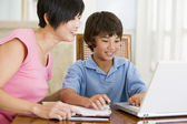 Woman helping young boy with laptop do homework in dining room s — Foto de Stock