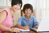 Woman helping young boy with laptop do homework in dining room s — Stockfoto