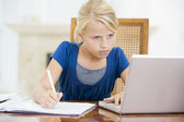 Young girl with laptop doing homework in dining room — Stock Photo