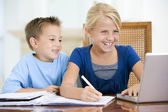 Two young children with laptop doing homework in dining room smi — Stock Photo