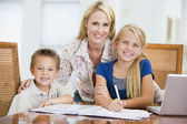 Woman helping two young children with laptop do homework in dini — Stock Photo