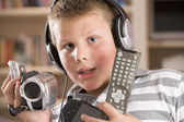 Young boy wearing headphones in bedroom holding many electronic — Stock Photo