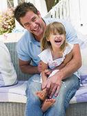 Man en jonge meisje, zittend op de patio lachen — Stockfoto