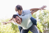 Man and young boy outdoors playing airplane smiling — Stock Photo