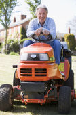Man outdoors on lawnmower smiling — Stock Photo