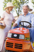 Couple outdoors with tools and lawnmower smiling — Stock Photo
