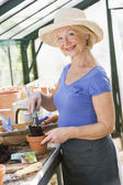 Woman in greenhouse putting soil in pot and smiling — Stock Photo