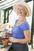 Woman in greenhouse putting seeds in pot and smiling — Stock Photo